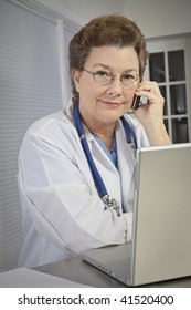 A female medical doctor at her laptop, talking on the phone.