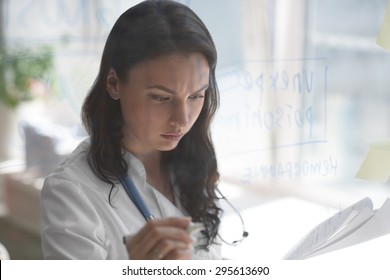Female medical doctor working at clinic office. Writing on glass whiteboard symptoms and test results of her patient to diagnose disease