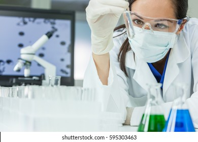 Female medical or research scientist or doctor using looking at a test tube of clear solution in a lab or laboratory