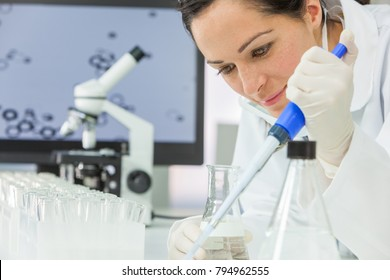 A female medical or scientific researcher or scientist using a pipette, flask and test tubes in a laboratory