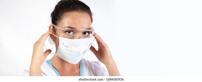 Weibliche Ärztin mit Schutzmaske, Schutzbrille und Zahnräder einzeln auf weißem Hintergrund. Frau Doktor oder Krankenschwester Tragen Schrott, Schutzmaske Gesichtsmaske und transparente Glocke.