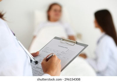 Female medicine doctor filling in patient medical history list during ward round. Medical care or insurance concept. Physician ready to examine patient and help. Patient sleeping