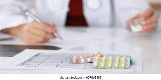 Female medicine doctor fills up  prescription form to patient closeup. Panacea and life save, prescribe treatment, legal drug store, contraception concept