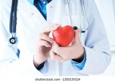 Female medicine doctor hold in hands red toy heart close -up. Cardio therapist student education concept