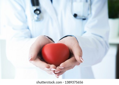 Female medicine doctor hold in hands red toy heart close -up.