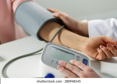 Female medicine doctor measuring blood pressure to patient. Patient communicates with physician doctor having medical examination. Medical concept. Hand of doctor and patient while pressure measuring