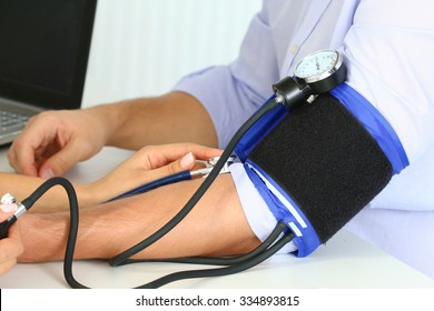 Female medicine doctor measuring blood pressure to her patient. Hands close up. Medical and healthcare concept