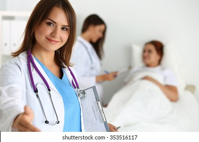 Female medicine doctor offering hand to shake while patient lying in bed communicating with doctor during ward round. Greeting and welcoming gesture. Medical cure and tests advertisement concept