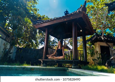 Female meditating by the pool, Bali, Indonesia.The girl sits in a gazebo at a bali in a lotus pose and meditates with a view of the pool.