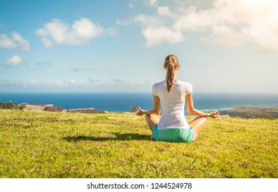 Female meditating in a grass field overlooking the ocean.