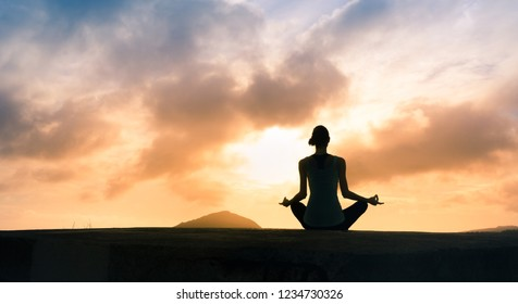 Female meditating on a rooftop at sunset.