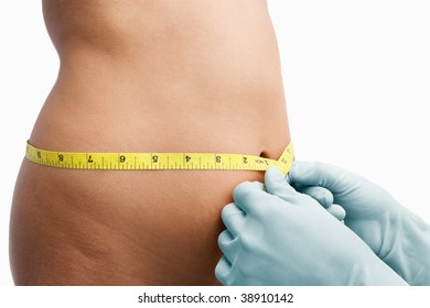 Female mid section being measure by doctor hand before liposuction over white background