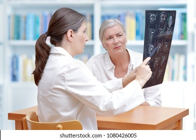 Female middle aged doctor discussing with her senior stroke patient ct-scan images of her brain