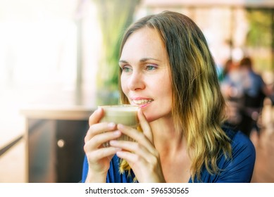 Female middle aged woman happy with her life and content with the future. No worries and drinking coffee in a restaurant or pub in a European setting. Bright and sunny image.