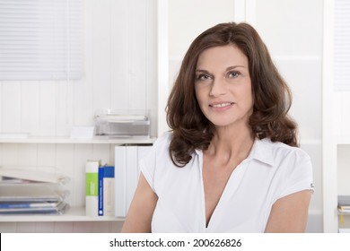 Female middle-aged doctor in portrait sitting at desk.