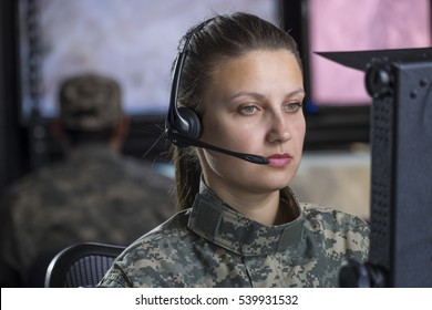 Female military drone operator on computer
