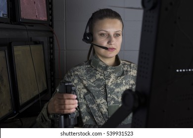 Female military drone operator working at computer