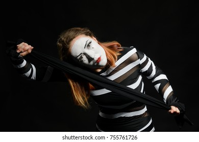 Female mime posing on black background. Waist up portrait of a pantomime actress, dancing in black and white costume, stretching a scarf.