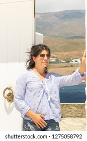 Female model against the island of Andros in Greece.