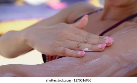 Female model apply sunblock cream on hand and shoulder, sitting on beach, cinematic dof