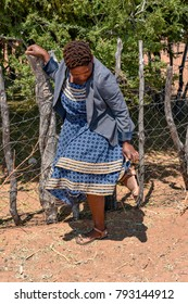 A female model from Botswana Africa posing standing with green vegetation in the background looking at her sandals wearing a blue dress at a cattle fence