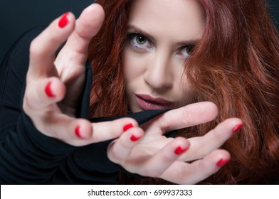 Female model with curly hair doing a hand gesture of taking something in closeup view