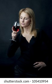 female model holding wineglass full of red wine