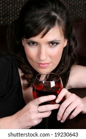 Female model with intense eyes holding a glass of red wine