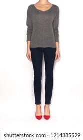 Female model isolated on white background wearing grey textured sweater with slim denim jeans and red high heel shoes