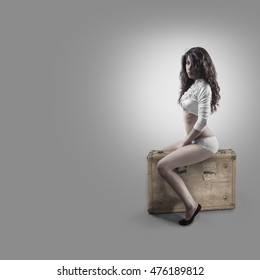 Female model with long black hair sitting on a baggage with nice gray background white short and white top. nice body wearing red lipstick.