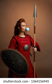 Female model looking away, blowing big blue bubble, chewing gum, holding spear and shield. Beautiful, brave woman with ginger hair standing, posing in studio, wearing in red medieval tunic.