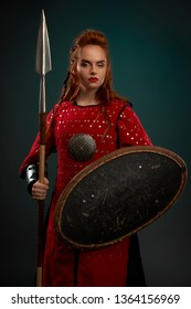 Female model looking at camera, holding spear and shield. Beautiful, brave and serious woman wearing in red medieval costume, tunic. Woman with ginger hair standing, posing in studio.