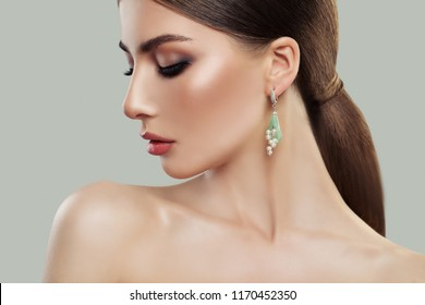 Female model with makeup and fashion jewelry earring with pearls. Beauty and accessories.