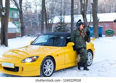 Female model in military uniform posing with gun near yellow sport car