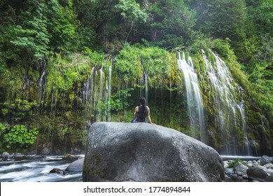 female model millennial resting during shelter-in-place at a waterfall in northern california