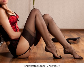 Female model from neck down in sexy silky lingerie, garter belt, and stockings sitting with beautiful legs and feet on wood floor