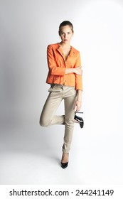 female model on white grey background with orange jacket
