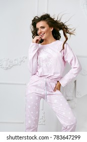 Female Model In Pajama. Woman In Sleepwear Clothing. Portrait Of Happy Smiling Girl With Beautiful Hairstyle And Natural Makeup In Stylish Home Clothes. Nightwear Clothing. High Quality Image