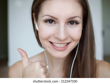 Female model posing for a picture on a white background studio with headphones.