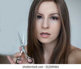 Female model posing with scissors on a white background with a strong look, closeup