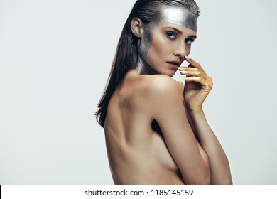 Female model posing topless with sliver color on face and hands painted with gold color. Sensuous woman with artistic makeup against grey background.