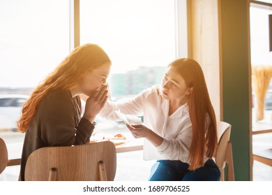 Female model sits in a cafe with her friend and blows her nose. Young woman is sick.