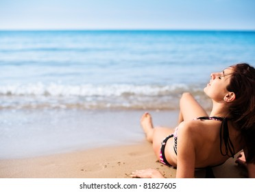Female Model, Sitting with her head back relaxing on the Sand at the beach, as the waves come in.