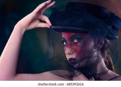 female model wacky red face paint voodoo vibe. black around eyes