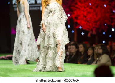 A female model walks the runway in beautiful white dress during a Fashion Show. Fashion catwalk event showing new collection of clothes.