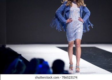Female model walks the runway in blue dress during a Fashion Show. Fashion catwalk event showing new collection of clothes. Single model. Blue dress.