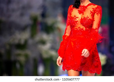 Female model walks the runway in a red dress during a Fashion Show. Fashion catwalk event showing new collection of clothes.