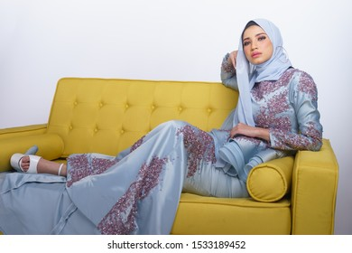 Female model wearing light blue peplum dress with hijab, a modern lifestyle outfit for Malaysian woman sitting on a couch isolated over white background. Wedding, lifestyle and beauty concept.