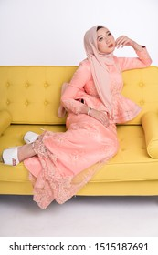 Female model wearing light peach peplum dress with hijab, a modern lifestyle outfit for Malaysian woman sitting on a couch isolated over white background. Wedding, lifestyle and beauty concept.