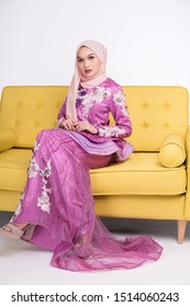 Female model wearing light purple peplum dress with hijab, a modern lifestyle outfit for Malaysian woman sitting on a couch isolated over white background. Wedding, lifestyle and beauty concept.